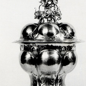 Chalice (a) with six double repousse swellings surrounded by wrigglework, gilded, on matching foot.  Stem, urn-shaped with three scrolled handles.  Silver cut and scrolled collars at junctions. Cover (b) silver-gilt with six swellings and cut and scrolled finial.