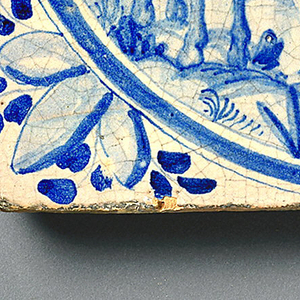 "Group of four tiles, square, with blue underglaze decoration on buff ground, each with name of one of the four continents, and corresponding allegory and attributes within a circular medallion: -72a, ""Asia,"" showing turbaned figure riding in a howdah on back of an elephant, with two attendants; birds in foreground, turreted architecture in background; -72b, ""Europa,"" showing a lady, cavalier and dog in foreground, watching woman in a sedan chair carried by two men; European style buildings in background; -72c, ""Africa"" with a turbaned man and woman, with attendant holding parasol, with the attributes of monkey, ostrich and camel; -72d, ""America"" showing an Indian in feather skirt and headdress, carried on a litter by five similarly but less ornately dressed Indians, and attended by one holding a fan; at left a conquistador on horseback, and a cockatoo on a branch; in right background, a sailing ship."