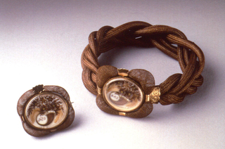 Band of tightly braided brown human hair hinged with gold mounts to oval framed decoration of pearls, pailettes, hair and the initials MAS in form of horn-of-plenty