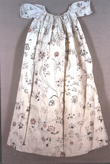 Infant's dress with a pattern of delicate floral sprays in blue, red, lavender, and brown on white. The skirt is gathered into a yoke, which has a draw-string neckline, with short sleeves; open down the back.