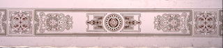 Border design in three shades of light brown distemper and one shade of darker brown flock. Symmetrical, sparse and etenuated strap-work patterns with shells and lion heads centering medallions in the pattern. Long horizontal rectangle with three groupings of strapwork alternates with square filled with centralized strapwork and foliage pattern.