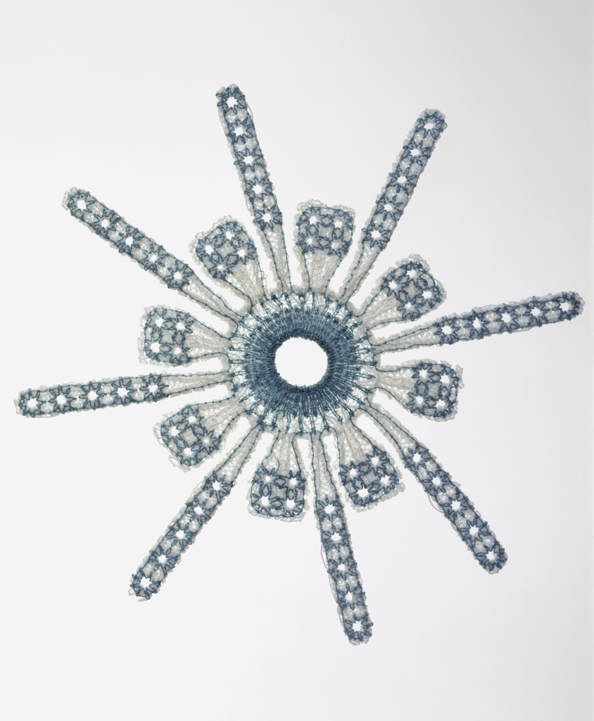 Bioimplantable device for reconstructive shoulder surgery in the form of a snowflake, with eight short and eight long projections from a center ring, machine embroidered in white and blue polyester with the base cloth dissolved for a lace-like effect.