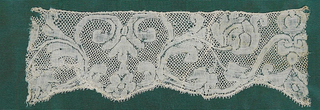 Fragment of Valenciennes lace has a symmetrical design of scrolling flowering branches and palmettes with scalloped border. Round mesh.