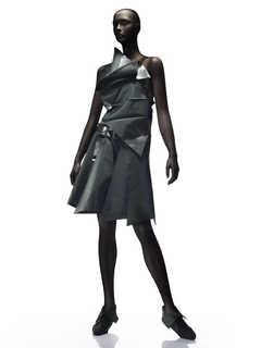 Asymmetrical sleeveless top and knee-length skirt with belt. Pleated gray polyester, some areas transfer-printed in silver.
