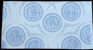 Small blue circular medallion containing landscape vignette within a wreath, printed in blue and white, resembling Wedgwood blue and white.