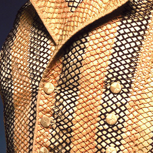 Men's double-breasted waistcoat with high standing collar, cut straight at the waist.  Waistcoat is patterned with stripes, and is comprised of the colors brown, peach, and cream.   There are seven worked buttonholes down front, with a row of matching silk covered buttons on either side. It is lined with unbleached cotton.