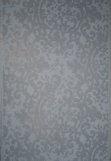 Intertwined scrolls and leaves in gray, studded with lines of golden dots, on white ground.