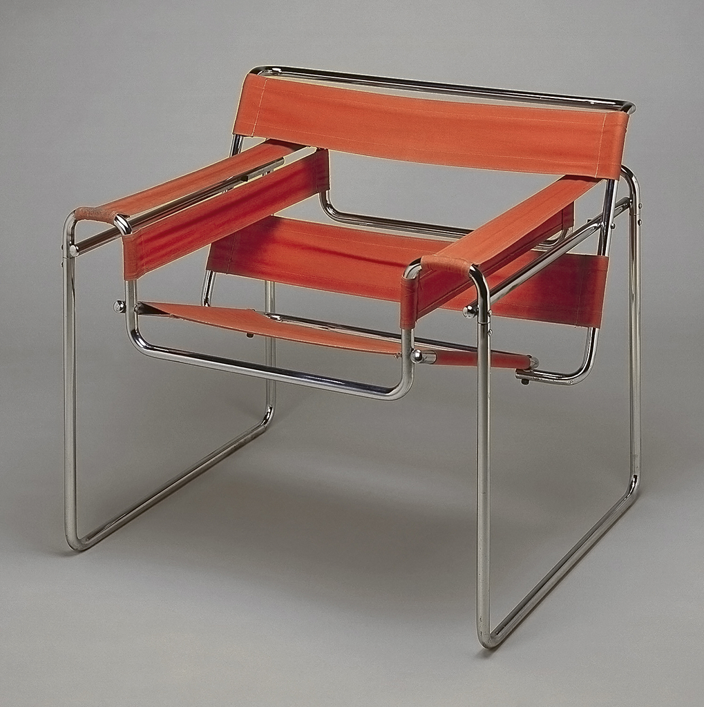 Rectilinear chair frame consisting of intersecting bent tubular steel elements secured with screws and nuts; orange canvas panels stretched over frame to form back, seat, and arm rests.
