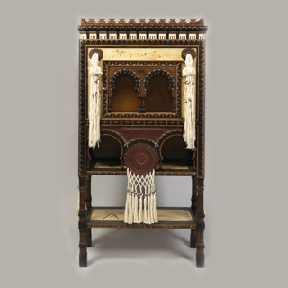Wooden cabinet with palmette crenellation on top. Double arched opening at upper shelf flanked by white textile tassels; lower shelf opening with two arcs and netting with tassels.