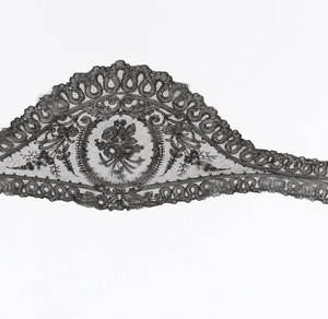 Shaped head scarf or fall cap of black Chantilly-style lace, with a floral motif in the center and at each end with flowering sprays and ribbons filling spaces, within a border of sharply curving bands. Chantilly style.
