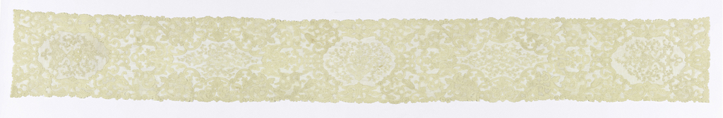 Table runner with a lace border showing floral bouquets enframed by swirling border pattern.