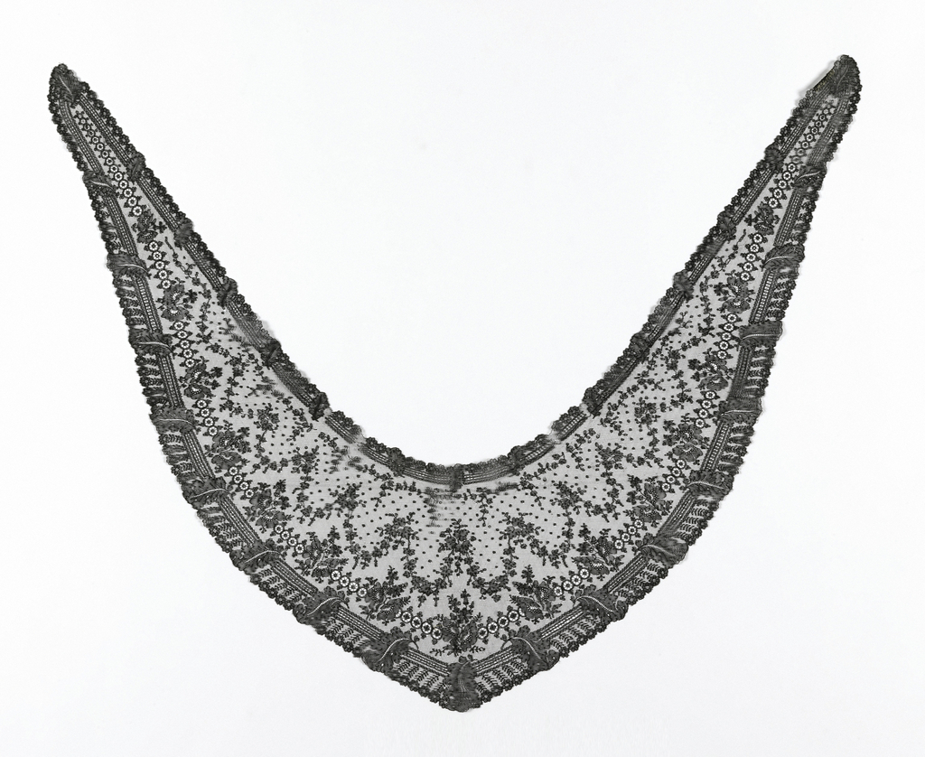 Shaped head scarf in black Chantilly lace showing pattern of garlands of floral sprays. Scarf outlined along edges by border motif of straight lines and repeated floral spray.