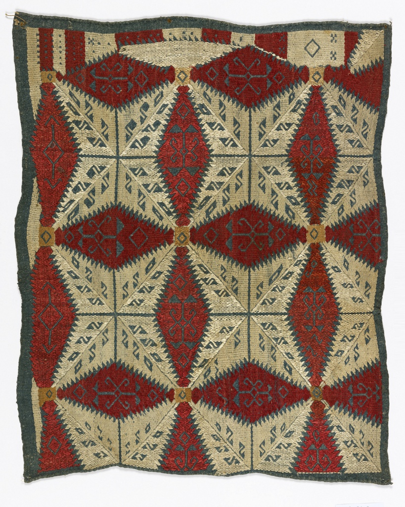 Cushion cover of heavy, hand-woven linen, dyed in indigo. Embroidered with red, white and buff silk in a geometric design of star and leaf forms. The motifs have saw-tooth edges, and contain smaller plant motifs reserved in blue linen.