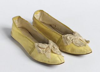 Pair of woman's slippers with yellow kid uppers and leather soles. Slippers have pointed toes, white silk ribbon bows and are lined with linen.