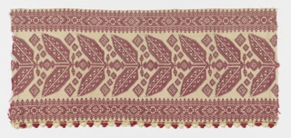 Fragment showing a stylized, symmetrical vine in red silk on a natural ground with red and white fringe.