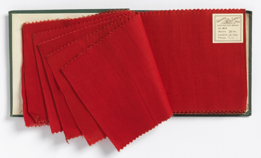 Bound manufacturer's sample book with eighteen swatches of dyed red cotton. Each swatch shows a progressive increase in density and weight of the twill woven cloth. Bound in blue leather with two brass rivets and a paper label reading Genuine Turkey Red with the logo of Sun and Lion Brand.