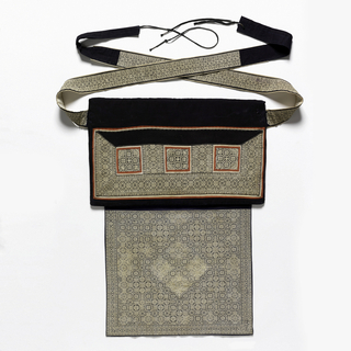 Baby carrier with an upper rectangular section stiffened with a reed mat, and a soft lower square, with long tying straps. The upper section is of blackish-blue cotton with red cotton appliqué around the outside and forming three squares, all filled with fine embroidered geometric pattern in white. The lower square and straps are indigo blue, embroidered all over with a diamond grid of fine white cross-stitch embroidery in geometric and floral forms. Back lined with several pieces of indigo-dyed cotton in varied shades. Straps lined with undyed cotton.
