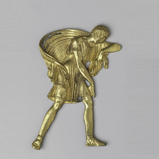 Furniture mount in the shape of a male figure walking into the wind with robes billowing.