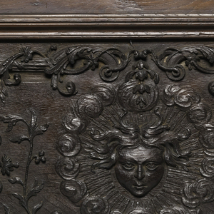 Panel with head in center, surrounded by sun-like rays; foliate patterns around.