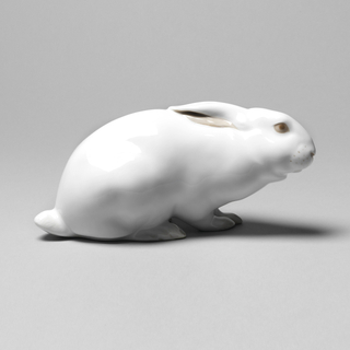 Figure of a crouching white rabbit with ears laying flat against its head; eyes, nose, muzzle, mouth and interior of ears picked out in shades of pink.