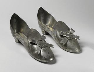 Pair of tin slippers on short heels; looped tin ribbons with nothced ends and stamped oval tin buckles mounted at tongues. Each heel, instep, back and sole made separately, soldered together.