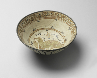On slight foot a slightly curved bowl of coarse whiteish clay, the lower part unglazed. Slight pinkish white glaze on upper outside and on inside; in center a bird painted in red and gold, in two red circles; at edge block script in red and gold. Black scrolls completing decoration; black lines forming arches on outside.