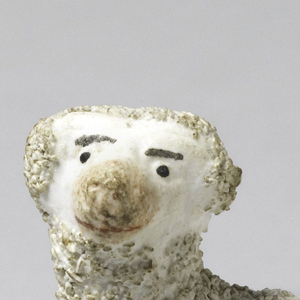 Textured figure of standing poodle, head turned to side, on simple oblong base; dog's features picked out in brown, tan, black, red on white ground, the curls of the hair in unglazed ceramic.