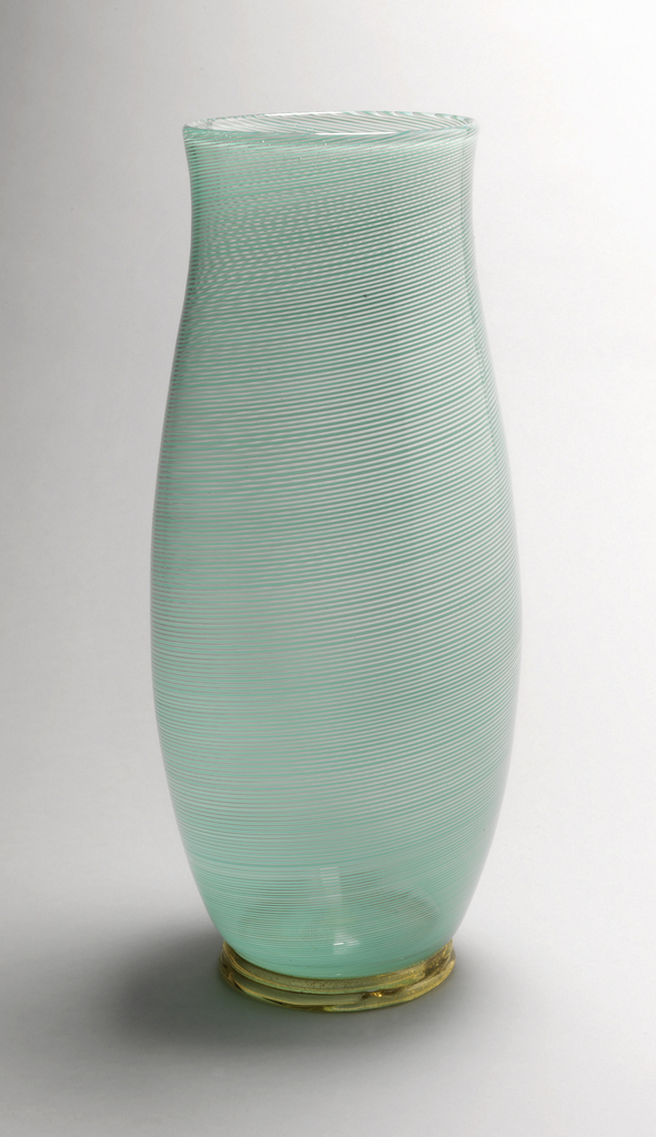 Curvilinear body composed of fine turquoise canes in clear glass, with applied loop ring foot in clear glass inset with gold leaf.