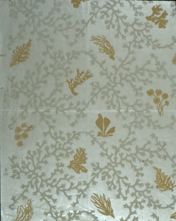 Cream-colored flock seaweed-like patterns enclose various designs of coral in yellow flock. On a glossy, cream-colored ground. One margin.