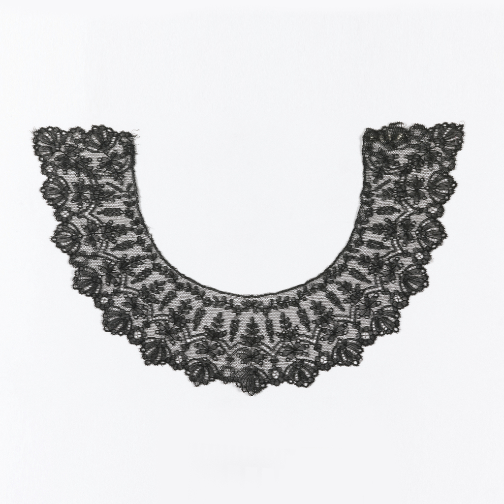 Round black collar with scalloped edges in a design of conventionalized flowers and foliage.