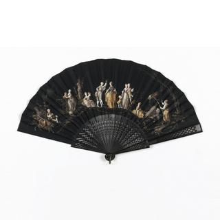 Pleated fan with leaf of black silk. Obverse: figures of men and women in landscape in the style of Boucher. Reverse: plain. Sticks are black pierced to form a lattice design with four-petalled flowers in interstices. Guards have a similar lattice design as on sticks.