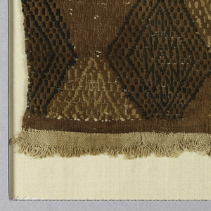 Coarse natural cotton with broad band divided top, center, and bottom with ribbed stripe. Large areas between with amorphous lozenges in black, blue and browns.