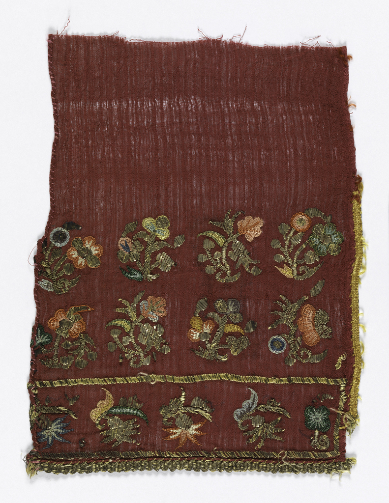 Sheer red muslin embroidered in floral border design in colored silks and metal strips and metal wound on silk in a variety of stitches.