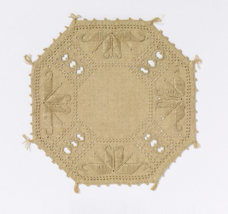 Eight-sided mat made of unbleached linen and ornamented with embroidery and bordered with woven picots and small tassels.