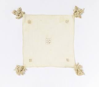 Cover with small squares of cutwork in the center and corners. Tassels attached to each corner.
