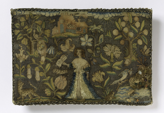 """Small cushion with a design showing a woman in the center with short brown hair and a blue and white gown worked in chenille thread. She holds in her right hand a scroll with the inscription: """"Faith."""" She is surrounded by oversized flower sprays. At lower right is a pool with a bird, and at left, a leopard. Above is a castle with mica windows. Background is worked in silver thread and sides edged with silver lace."""