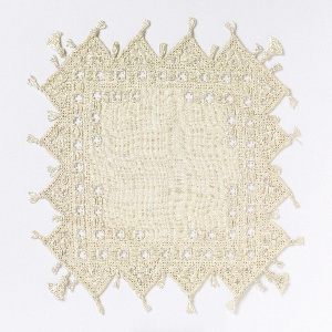 Small cover with broad sawtooth edges decorated with white linen embroidery, tassels and fringe.