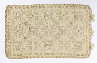 Cutwork pillow cover with squares containing an alternate arrangment of birds and geometric flowers.