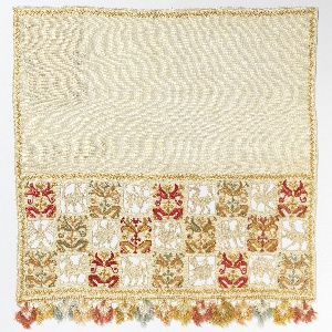 Small panel (as if one end of a towel) with a 3 row band of embroidered squares with plants in colored silk, alternating with squares of cut fabric filled with needle made (looping) animals and birds.  The 3 rows are offset. Bobbin made lace decorated with lace tufts of various colors attached to bottom.