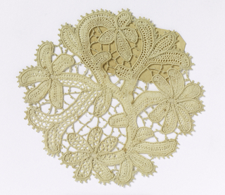 "Circular lace doily in the form of a flowering plant. Couched cord for raised outline and needle made ""brides"" and ""picot"" edging."