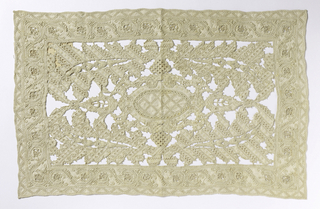 Rectangular panel of cutwork, deflected element and withdrawn element with embroidery. Horizontal and vertically symmetrical scrolling leaf with central medallion. Curving vine border.