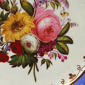 Circular form with scalloped edge and shallow well; wide rim glazed light blue, molded with five floral sprigs and scalloped edge, reserved in white; edge picked out in gilding; in center, a polychrome bouquet encircled by gilded vine motif, all on white ground.