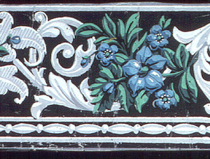 Pink and blue flowers alternating with grisaille acanthus scrolls. A row of strung beads is below.