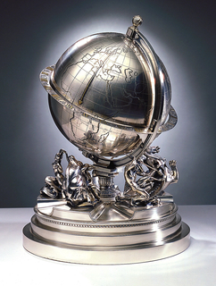 Terrestrial globe on stepped circular base with figures representing the Five Continents: Asiatic woman with five-headed cobra, Europa with the Bull, African hunter with lioness, American Indian on horseback, South Sea Islander on dolphin. Globe encircled by twenty-four-hour equatorial dial with the signs of the zodiac. Silver gilt arrow on globe indicates the time. Winding key also serves as a finial.