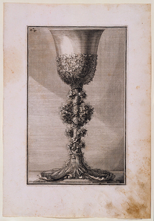 Engraving of a chalice with a base and stem composed of a sheaf of wheat, the grains splaying out to form a base. A grapevine encircles the stem and extends around the base of the cup. Designer's and publisher's names along bottom.