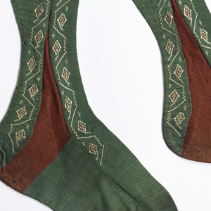 Pair of green knitted silk stockings with a red insertion at the ankle surrounded by embroidered decoration in pink and white.