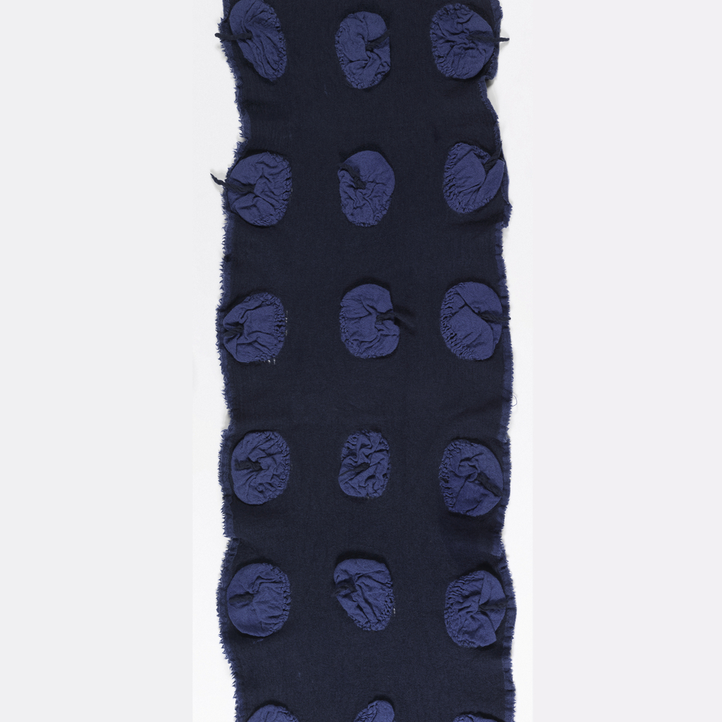 Front: Dark blue felted wool and regularly spaced light blue, puckered, circular pockets that have a protruding dark blue yarn in the center.
