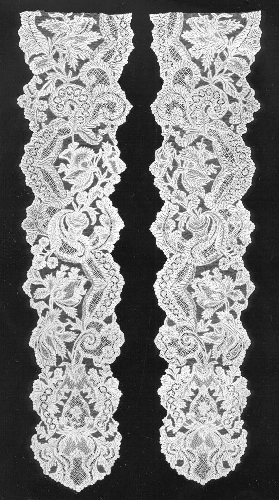 Cap streamers of Point de Venise à Réseau in an asymmetric design of floral and foliated forms are flanked at intervals by scalloped garlands, emerging from a geometrically-shaped base. Fond: réseau. Modes: réseau mouche, portes, fond de neige.