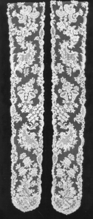 Brussels-style lace in a design that shows asymmetric volutes placed intervals terminating in complex floral sprays.