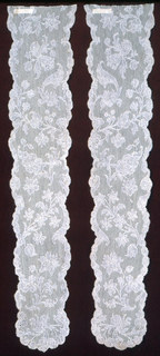 Cap streamers of Binche lace in an asymmetric, open floral pattern framed by narrow garlands that terminate in abbreviated scrolls.